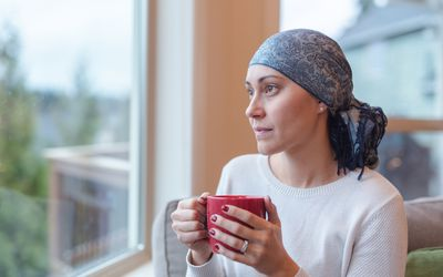 Woman with head scarf on looking out window