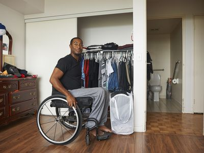 African American man in wheelchair smiling near bedroom closet
