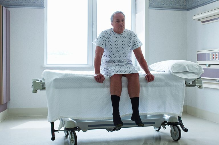 Senior man sitting on bed in hospital room
