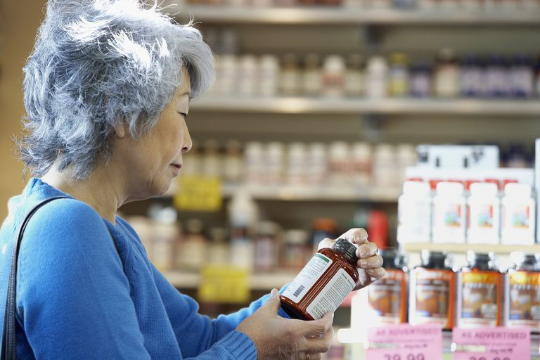 senior Asian woman looking at vitamin bottle in pharmacy
