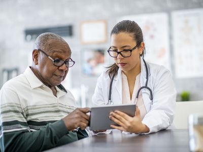 A senior black man is sitting in his doctor's office and listening as the doctor shows him something on a digital tablet.
