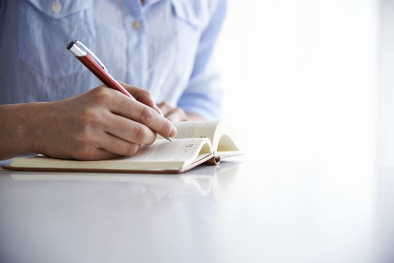 Close-up shot of a hand holding a pen, about to write in a diary.