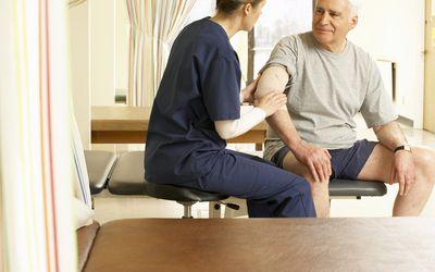 Nurse examining man's elbow