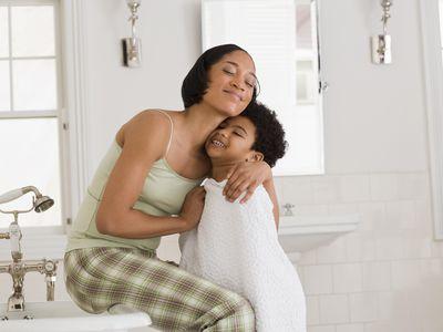 Mother hugging son in bathroom