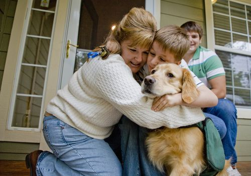 Mother hugging autistic son and guide dog
