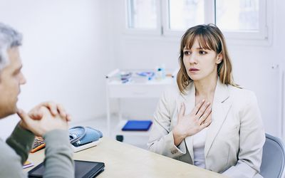 Patient explaining wheezing to doctor