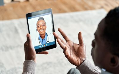 Over shoulder view of man video calling female virtual doctor.
