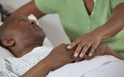 Black wife comforting husband in hospital