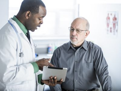A doctor discusses a new diagnosis with an older male patient.