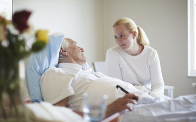 Daughter talking to her father in a hospital bed