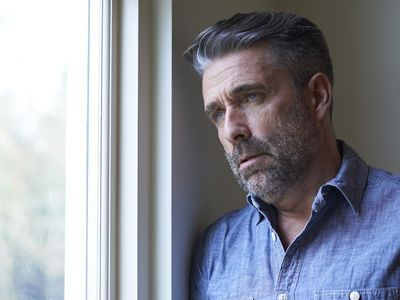 Mature man looking depressed and confuse staring out a window