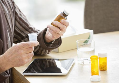 senior man looking at medications