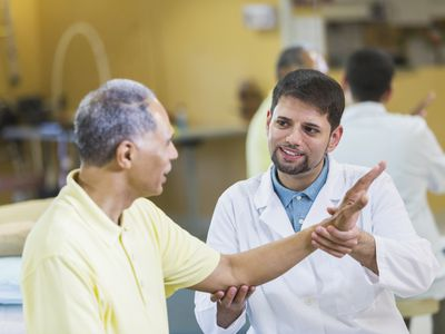 Physical therapist helps older man's range of motion for elbow