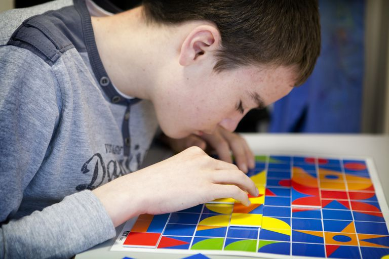 Autistic adolescent working on a tanagram puzzle