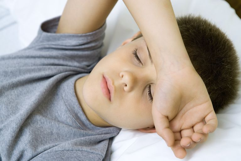 Boy lying down with arm covering forehead