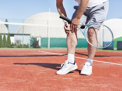 Tennis player holding knee in pain