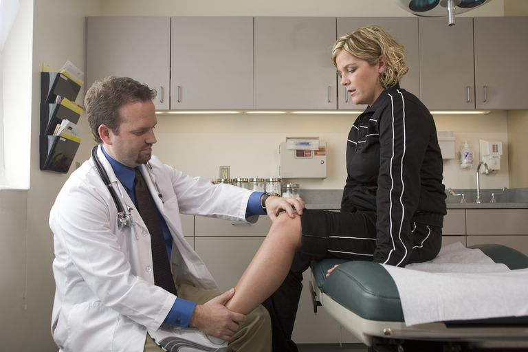 Doctor examining female patient's leg.