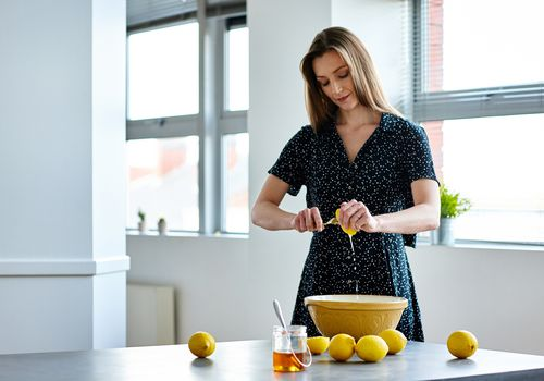 Beautiful mature woman preparing lemon juice at home