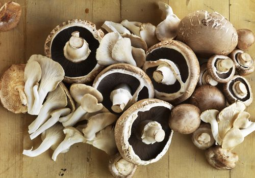 Photo of assorted fresh, whole mushrooms on a wooden table
