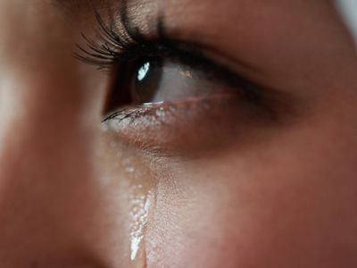Picture of one eye with a tear streaming down the cheek.