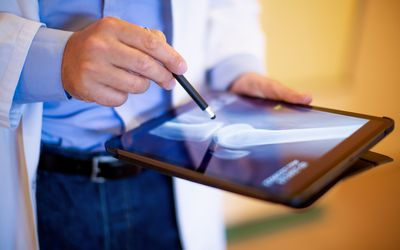 Cropped shot of doctor reviewing patients leg x-ray on his tablet pc