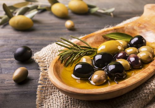 Mixed olives and oil in a wooden dish with rosemary