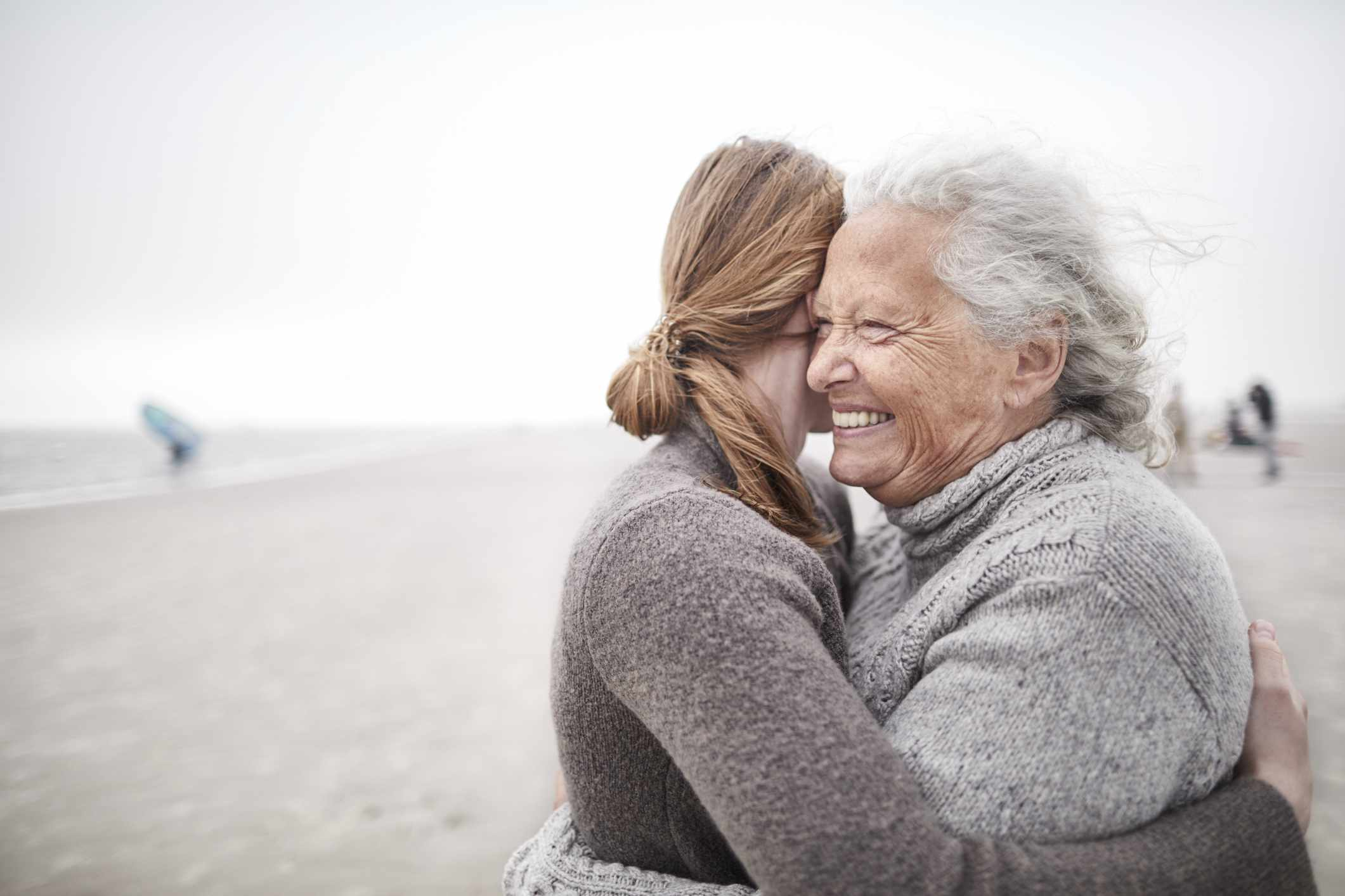 Affectionate grandmother and granddaughter hugging on the beach