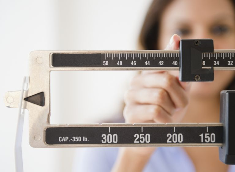 Woman using scale to weigh herself