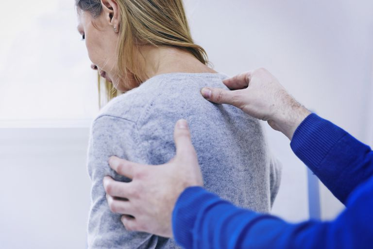 woman having her spine checked by doctor