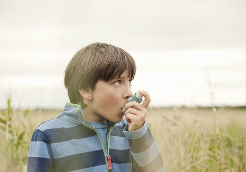 young boy using Asthma Inhaler in a field