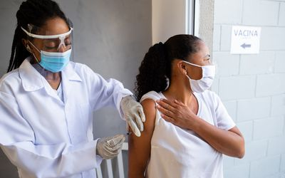 A Black healthcare worker with a face shield and gloves giving a vaccine to an older Black woman wearing a mask.