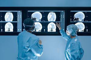 Two doctors examining a brain scan of a patient.