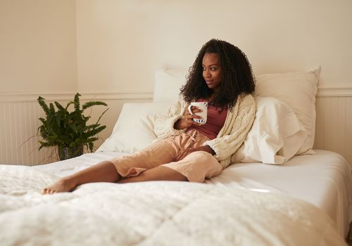Young Black woman cozy on her bed with a mug of tea.