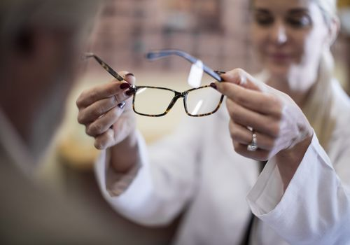 Optician helping customer to choose new spectacles