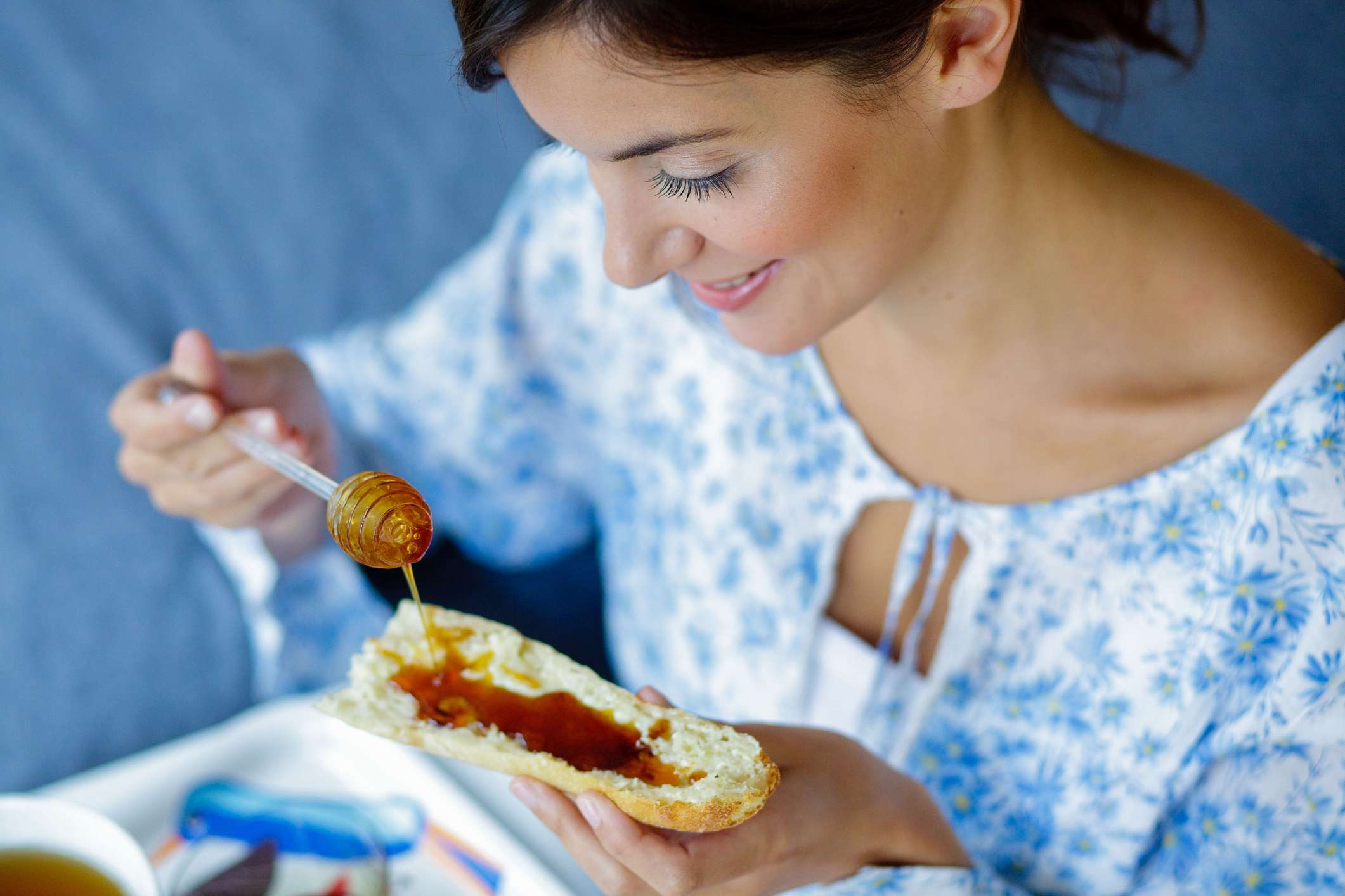 Woman pouring honey on a piece of bread