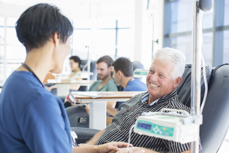Senior patient undergoing medical treatment talking to doctor in outpatient clinic