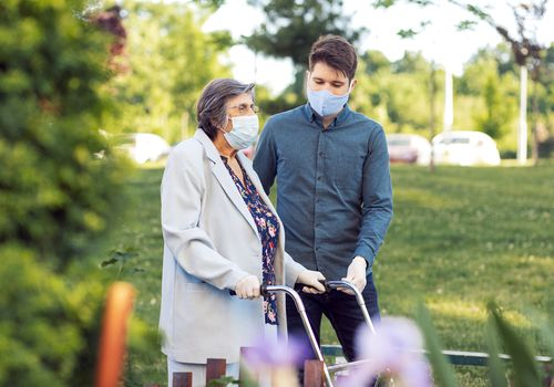 Man helping older woman with walker wearing masks.