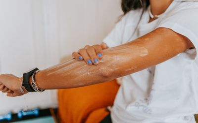 Woman putting sunscreen on her arm.