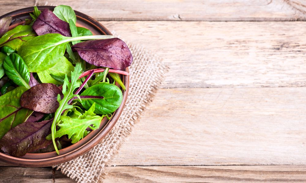Mixed salad leaves on wooden rustic background with top view. Healthy food, healthy lifestyle and diet concept. Fresh green salad with spinach, arugula, chard leaves, lettuce