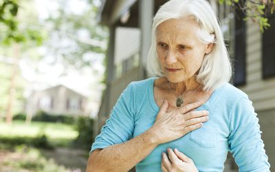 An older white woman in a light blue shirt standing outside with her hand on her chest
