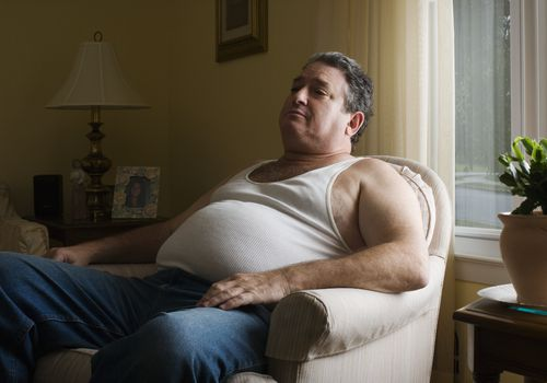 An overweight man sitting in his armchair