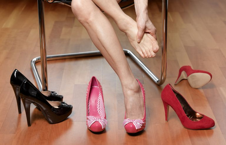 a woman rubbing her foot while trying on shoes