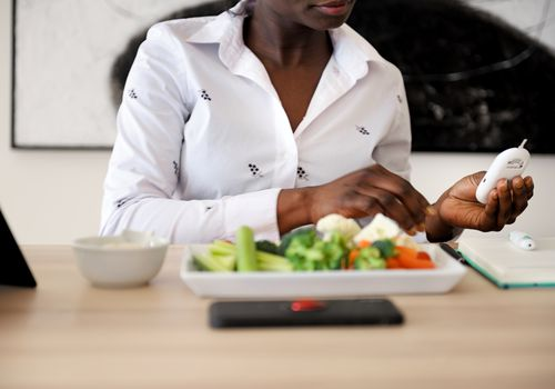 A Black woman (her face is not fully visible) checking her blood sugar, there is a plate of vegetables on the table in front of her.
