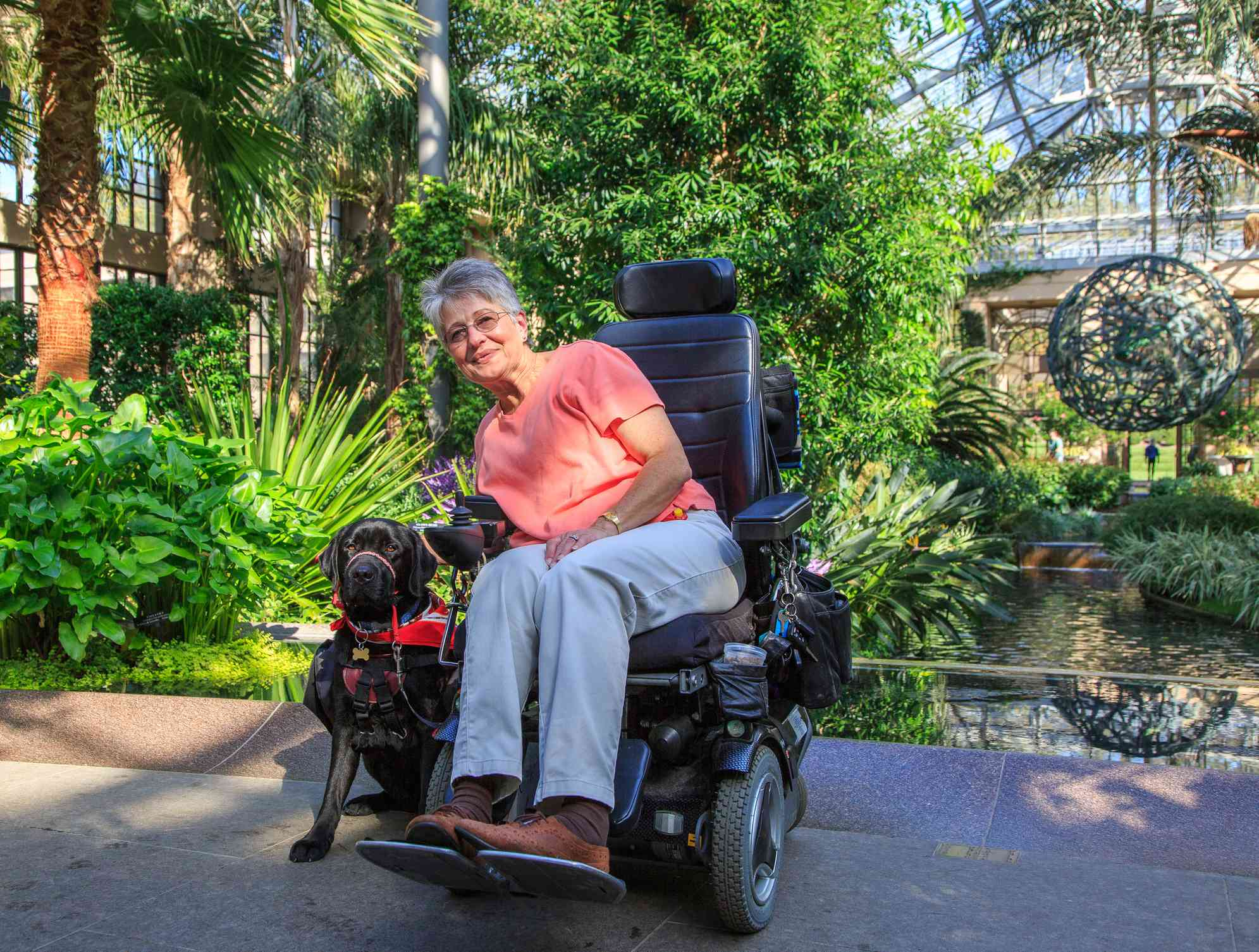 Woman in a motorized wheelchair petting her service dog outside in a park