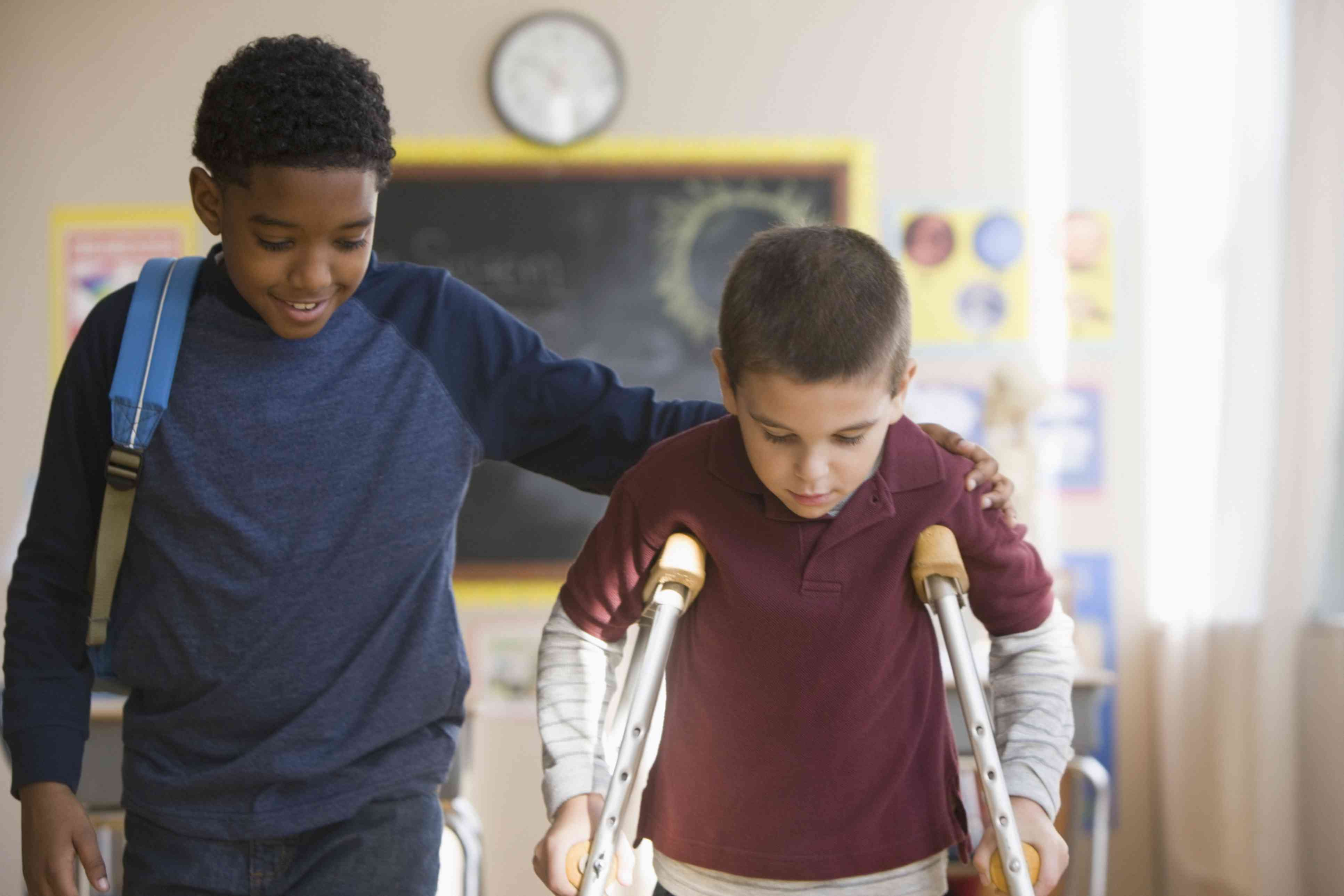Boy helping friend with crutches