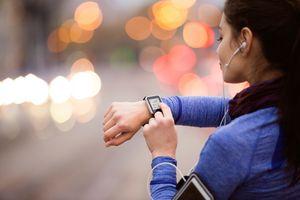 woman checking smartwatch on run