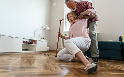 Old men helping wife who falled down on floor - stock photo