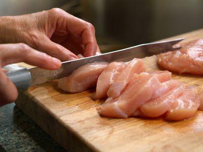 Woman Cutting Raw Chicken on a Wooden Cutting Board