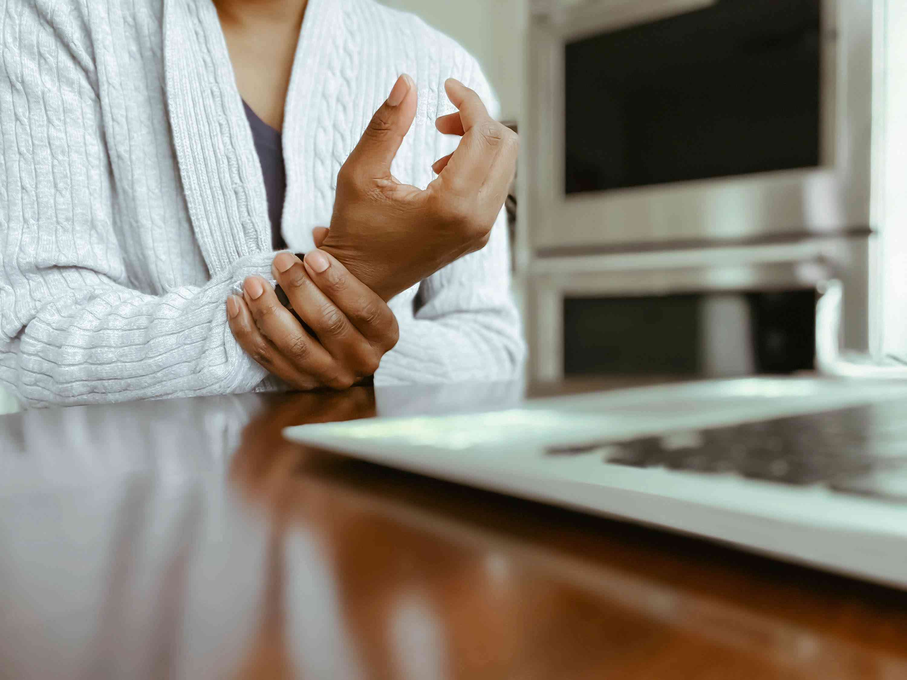 Woman Using Laptop Holds Wrist in Pain
