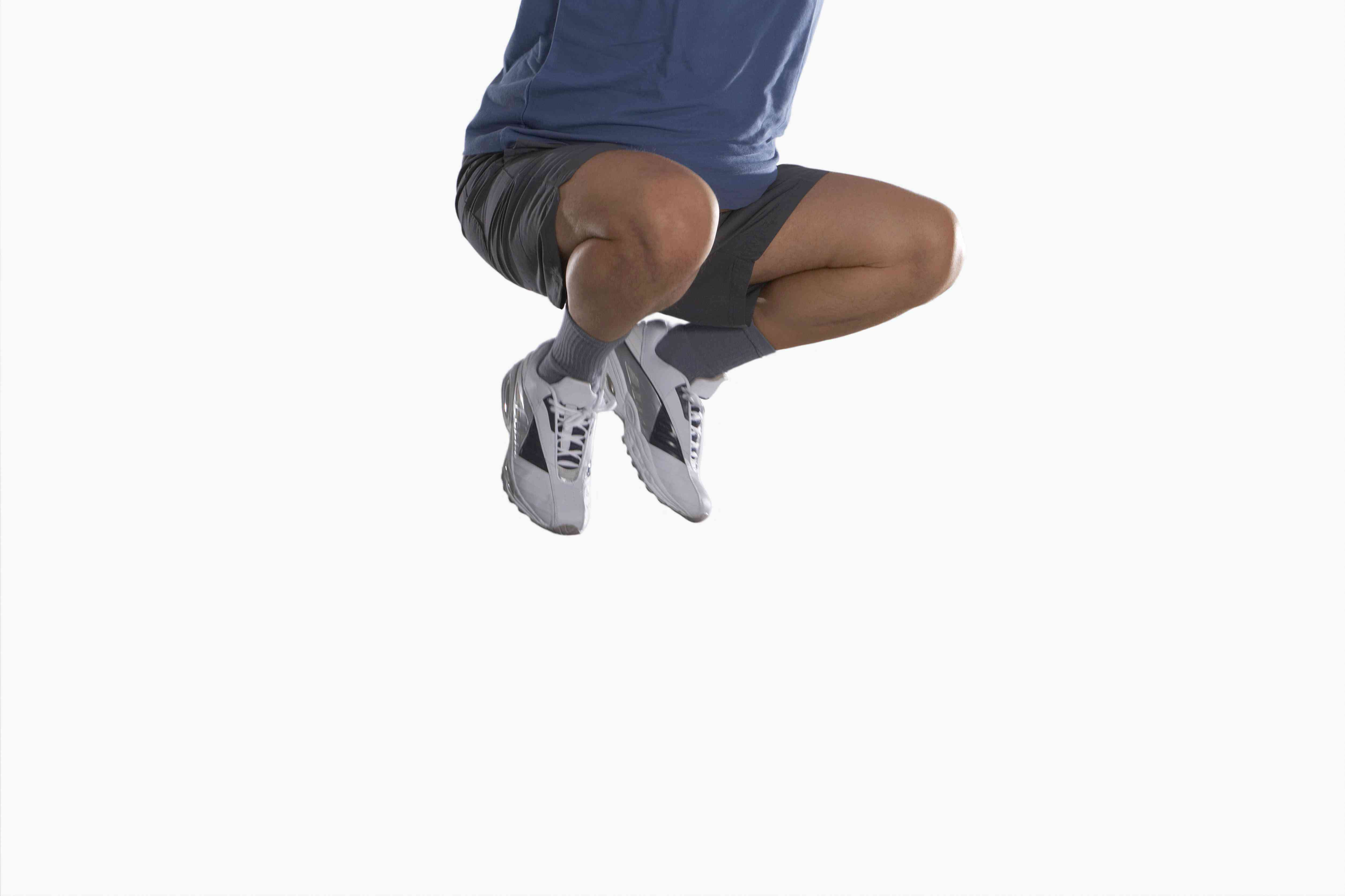 Man in athletic clothes jumping as high as he can on white background